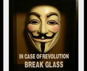 "A Guy Fawkes mask from ""V For Vendetta"" in a case with the label: ""In case of revolution: break glass."""