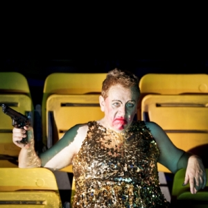 A fat man in drag, with a gun, with smeared makeup in a movie theatre