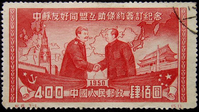 A red Chinese stamp showing Stalin and Mao shaking hands.