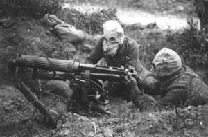 a picture from WWI - two soldiers with gas masks firing a machine gun