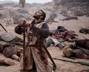 Knight covered in blood on a battlefield strewn with bodies