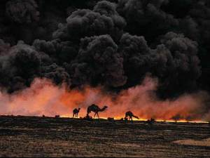 camel silhouettes against black smoke and oil fire