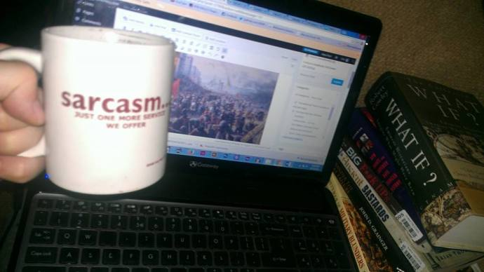 Back to work - me raising a mug (that says 'Sarcasm - just another service we offer'), in front of my laptop, next to a stack of history text books...