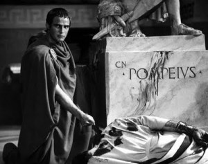 Brutus holding a knife over Caesar's bloody body, at the foot of Pompey's statue.